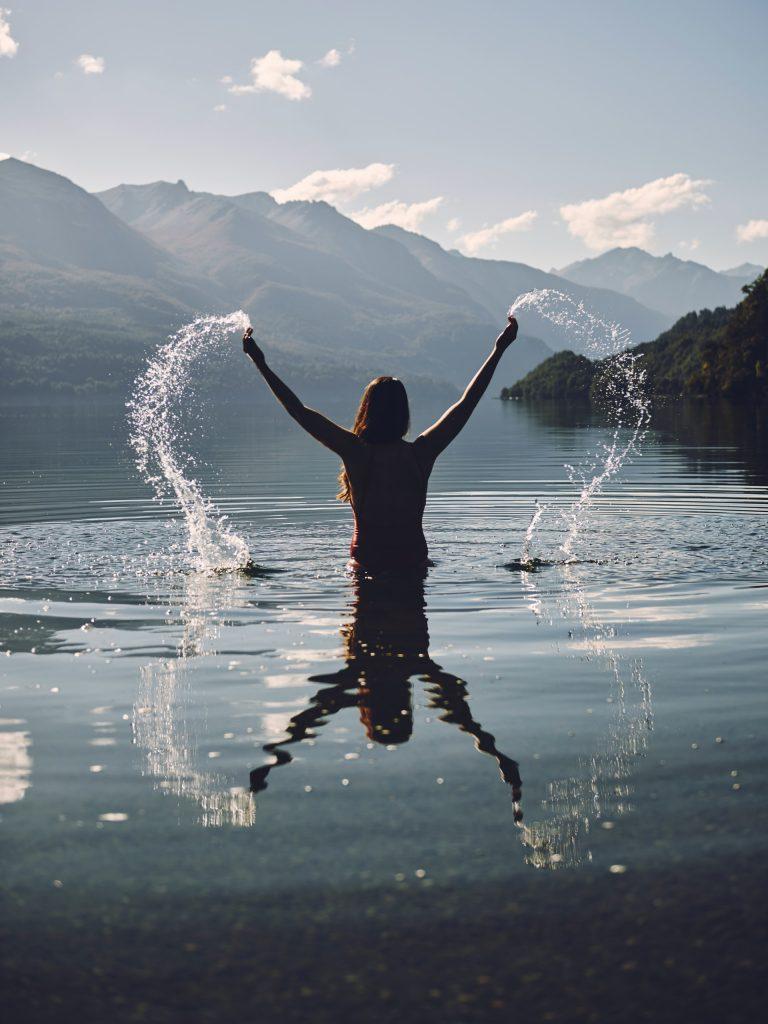 Femme dans un lac devant les montagnes