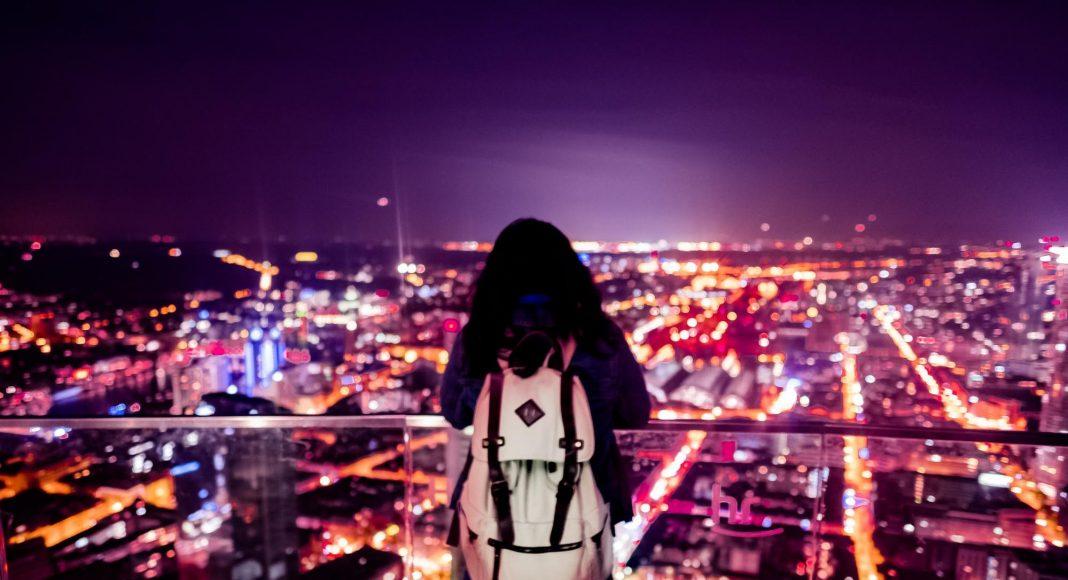 Femme regardant la ville la nuit